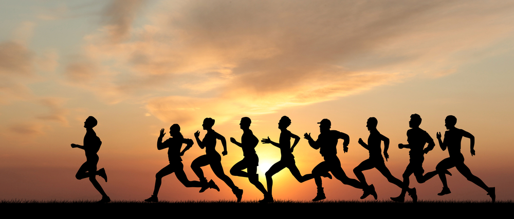 Group of runners in silhouette against a sunset